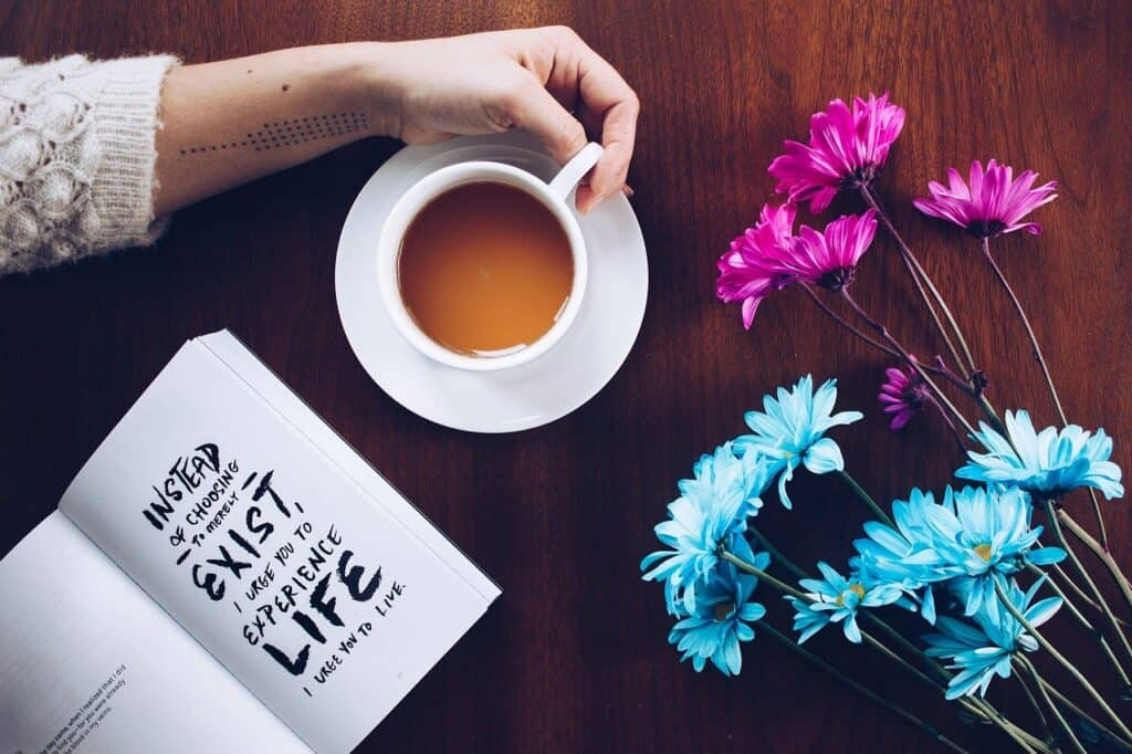 Cup of coffee, flowers and a diary to stay motivated